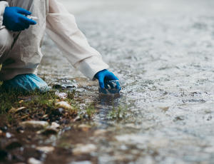 Scientist in protective suite taking water samples from the river / Photo © hedgehog94/Adobe Stock